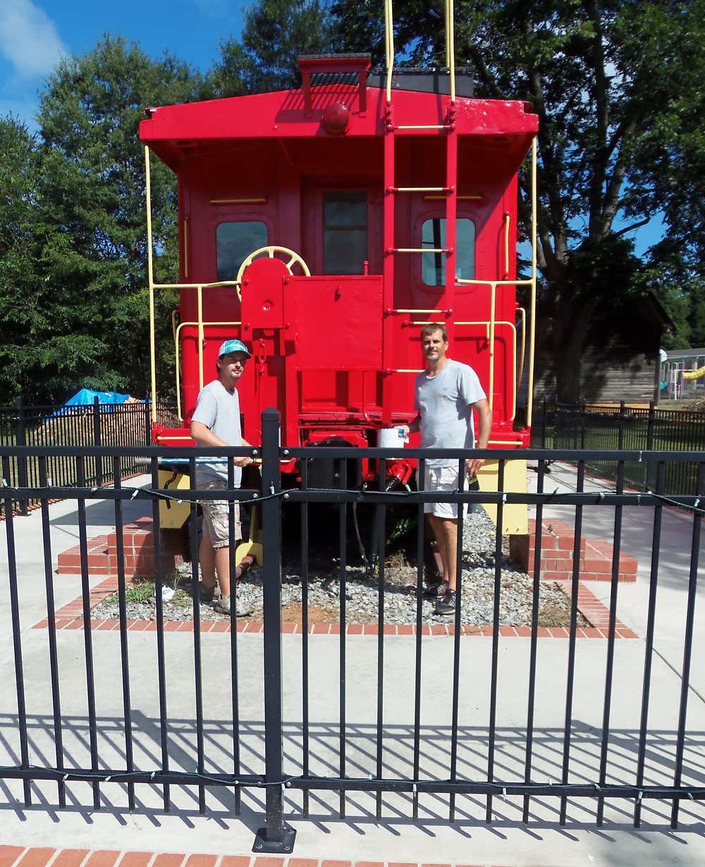 Austin McCurry and Jeremy Creswell of #1 Painting posing in front of the freshly painted caboose.
