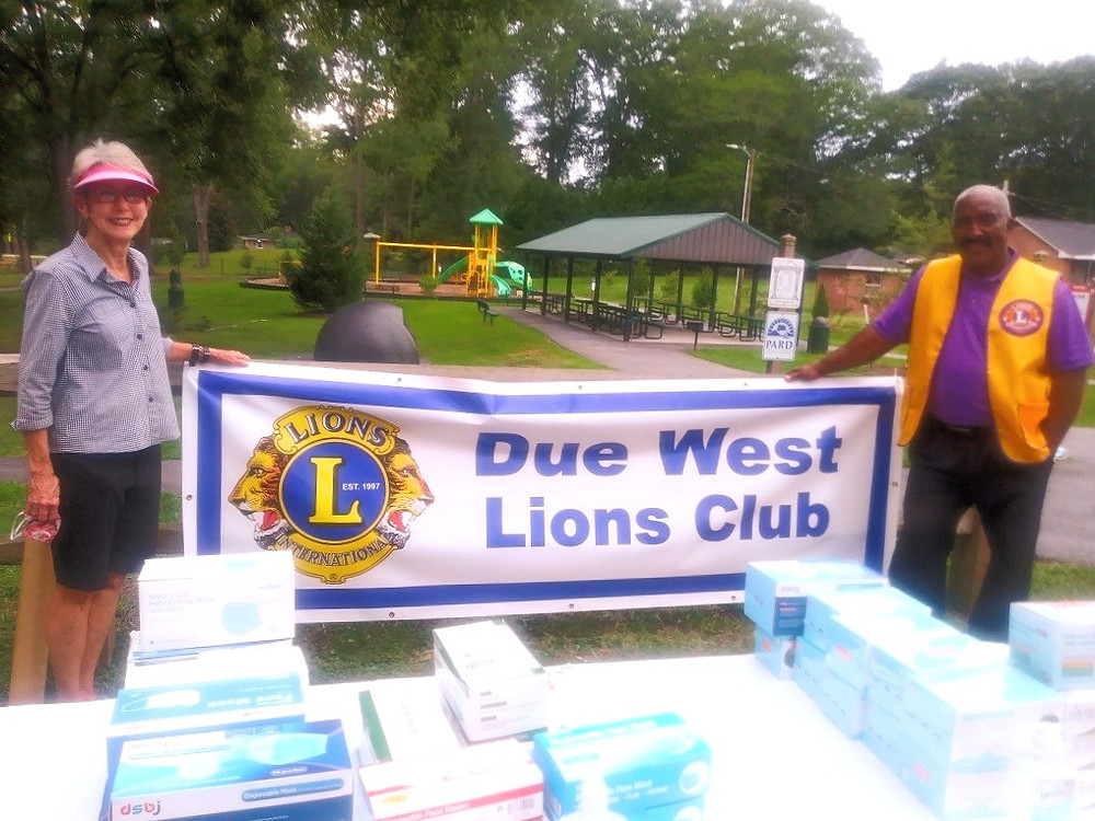 "Due West Lions Effie Jordan (left) and Amos Cunningham hold up a banner: ""Due West Lions Club"""