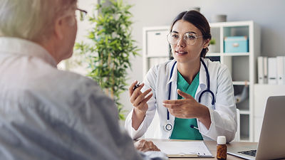 Physician Speaking To Patient In Office.
