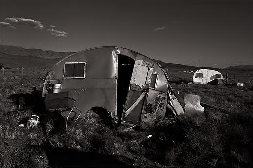 LAST TO LEAVE - B&W photo by fine art photographer Scott Lockwood of vintage trailers deteroriating in Keeler, CA field.