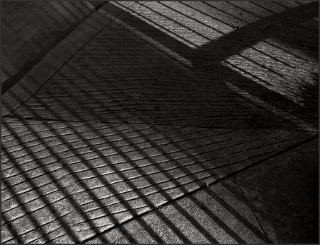 ABSTRACT SHADOW PATTERNS ON SIDEWALK - B&W photograph by fine art photographer Scott Lockwood.