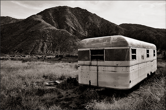 LISTENING TO THE CRICKETS SING - B+W photograph of the front of a vintage, 1950 Universal travel trailer by S.F. Bay Area, fine art photographer Scott Lockwood, looking very abandoned in an Indio, CA field.