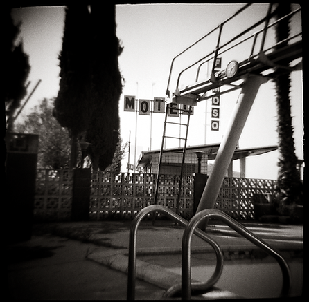DIVING BOARD, LADDER AND MOTEL SIGNS - B&W, toy-camera photo by fine art photographer Scott Lockwood of Famoso Motel.