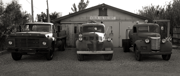 READY TO ROLL? - B+W photograph of three, unrestored, vintage, fire trucks in front of a distressed looking, Keeler Volunteer Fire Dept. bldg by S.F. Bay Area, fine art photographer, Scott Lockwood.