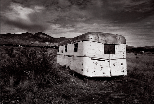 NEVER LOOK BACK - B+W photograph of the rear of a vintage, 1950 Universal travel trailer abandoned in an Indio, CA field by S.F. Bay Area, fine art photographer, Scott Lockwood.