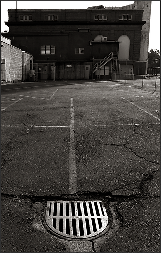 b+w tri-tone photograph of steel drain grate in parking lot of mare island naval shipyard by bay area fine art photographer scott lockwood.