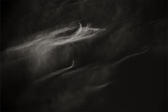 SOMEWHAT CURIOUS - B+W photo by fine art photographer Scott Lockwood of wind swept clouds.