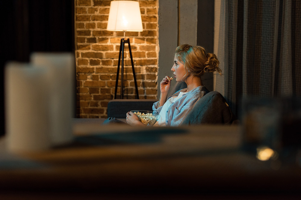 A woman avidly watches television. Image credit - iStock