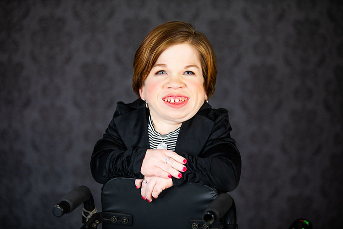 Kendra facing the camera leaning on the back of her wheelchair smiling