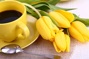 Yellow cup of coffee and yellow tulips