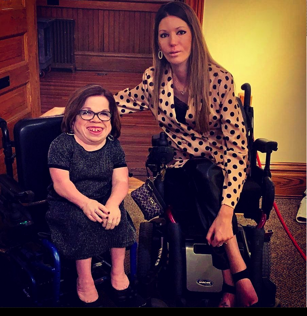 Two females in wheelchairs posing for a photo at a gala