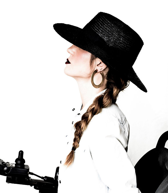 Side profile of female with a shiny black hat with a white shirt and long braided hair. She is sitting in a wheelchair.