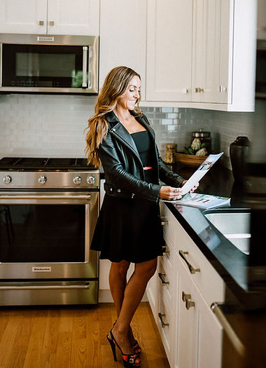 Marla standing in a beautiful kitchen and smiling while looking at an open house brochure