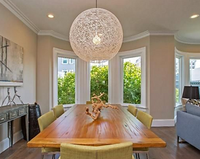 Open living and dining room with beautiful round chandelier over dining table and large curved windows
