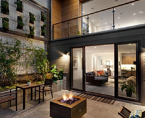 Rear exterior facade at night with burning fire pit