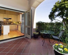 Exterior facade of kitchen and attached private paved patio through large open french doors