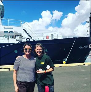 Bailey Ferguson and Michelle Schwengel-Regala in front of Schmidt Ocean Institute's Research Vessel Falkor, berthed at Honolulu Harbor in 2019.