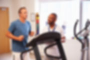 Man on treadmill receiving a health and fitness assessment from physical therapist