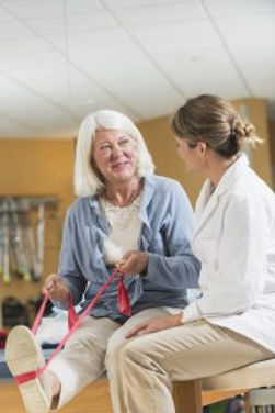 Elderly woman exercises with physical therapist
