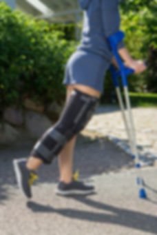 Woman walks with lofstrand crutches after knee surgery
