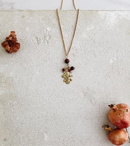 English oak leaf pendant in brass and dark red-brown gemstones