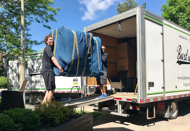 Two of our movers loading a sofa into our truck during a residential move in Montreal.