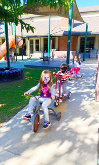 Children riding their tricycles and scooters