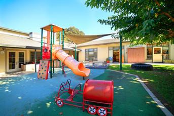 Outdoor Play Yard at St. John's Nursery School (Preschool).  Orange slide, rock wall, grassy area.