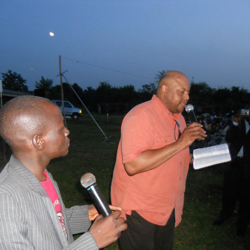 Apostle Ashford (right) preaches at village crusade with interpreter.