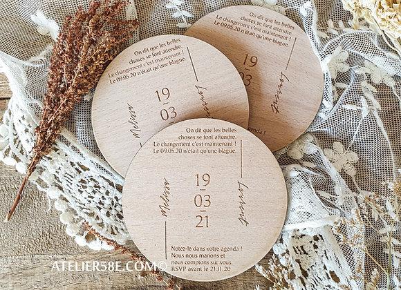 Vue du dessus de trois save the date en bois gravés pour un report de mariage