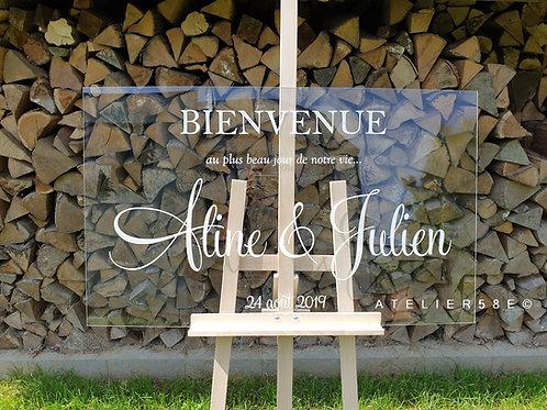 Panneau de bienvenue transparent pour mariage posé sur un chevalet en bois