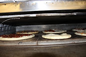 Picture of our pizzas being cooked in the oven.