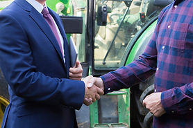 Farmer And Businessman Shaking Hands Wit