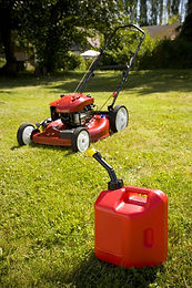 A red lawn mower and gas can in fresh cu