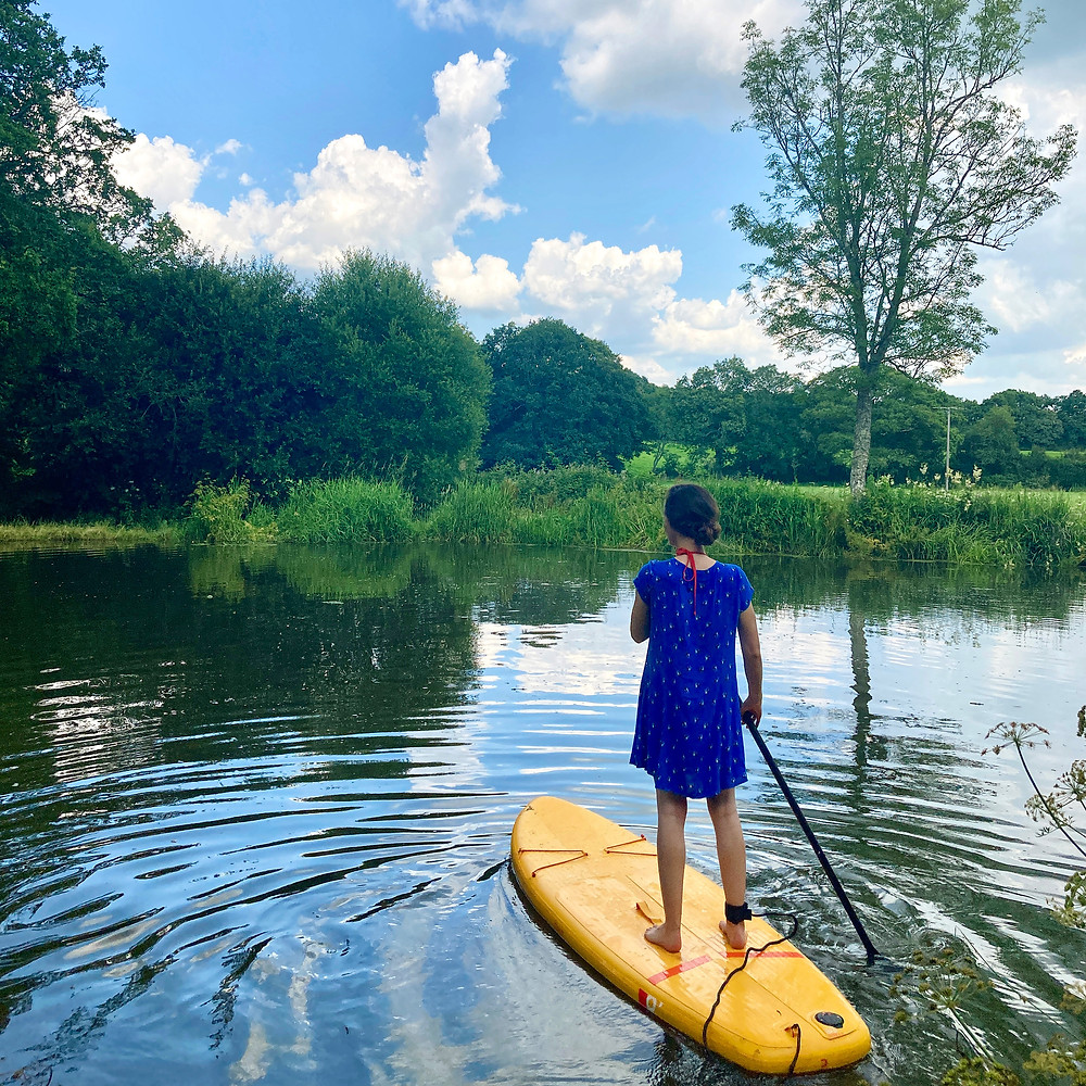 Emma Christopherson Art - Emma on a yellow paddle board on a canal surrounded by trees and nature.