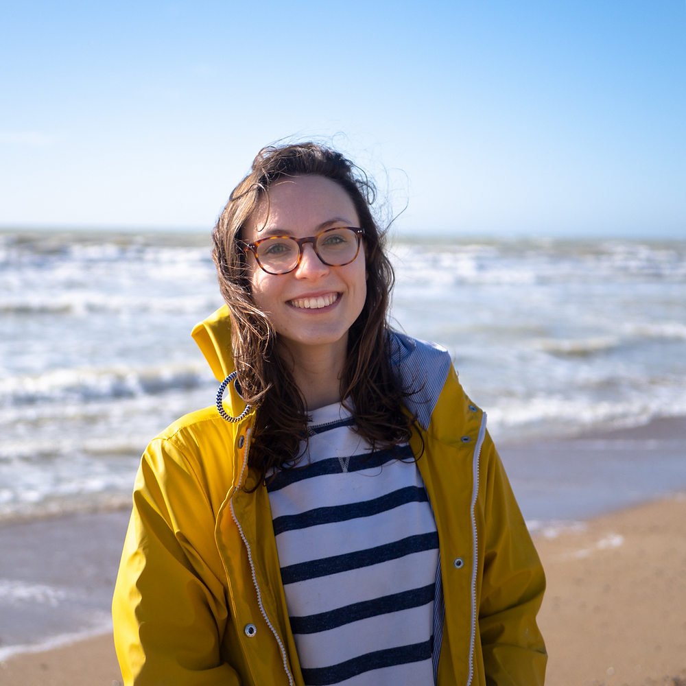 Emma on the beach wearing a yellow raincoat and stripey jumper