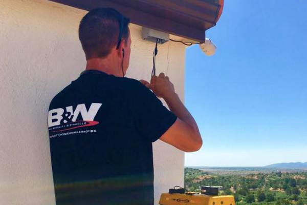 B&W employee inspecting external CCTV camera