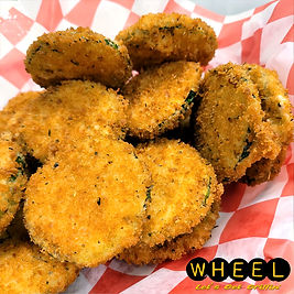 A basket of hand-battered zucchini chips served with tomato bisque and ranch dipping sauce.