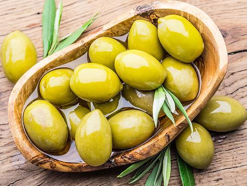olives vertes entières dans un bol d'huile, vue de dessus