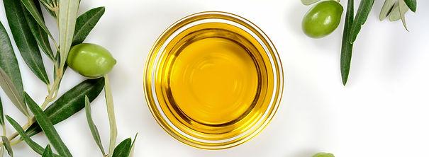 huile d'olive dans un bol, rameau d'olivier, olive verte
