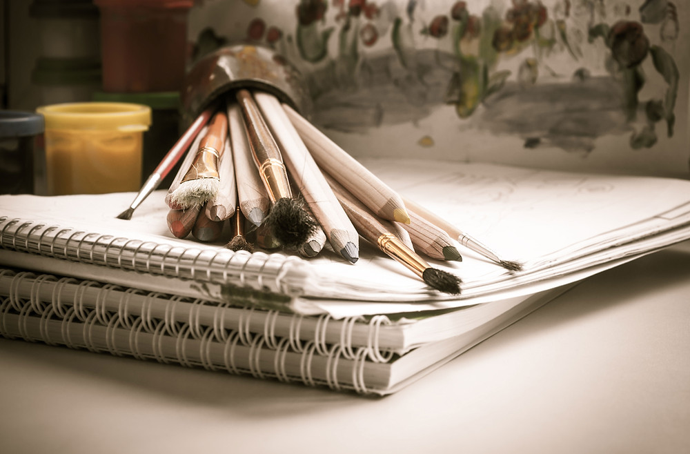 Artist tools like pencils & brushes sitting on sketch pads