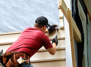 Young homeowner installs siding to his h