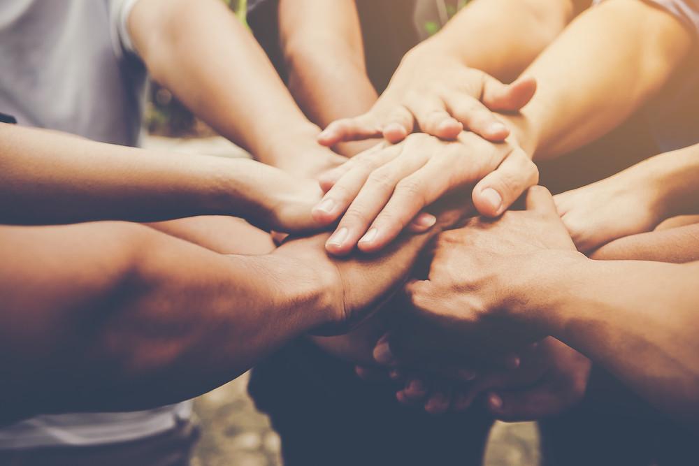 grupo de pessoas com mãos sobrepostas, como um time