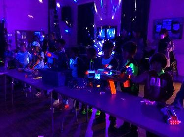Ultra violet lighting with children shooting nerf guns