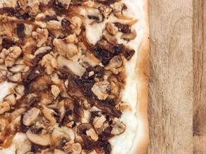 Pizza con base de quesos blancos, cebolla caramelizada, champiñones y bacon crujiente