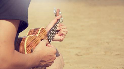 Canva - A Man Playing Ukulele on the San
