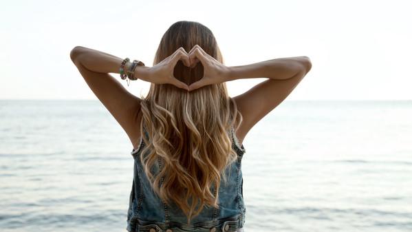 Heart shape hands, blonde hair with low sephia effect. Symbol of.jpg