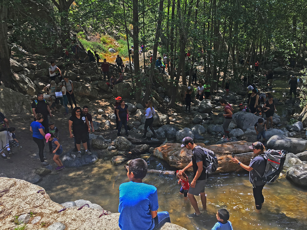 A crowd of people gather around the Eaton Canyon swimming site on Memorial Day 2018.