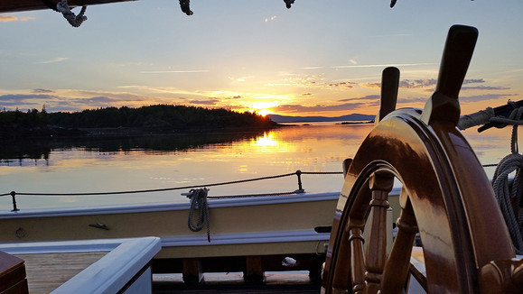 A beautiful Maine sunset behind the ship's wheel.
