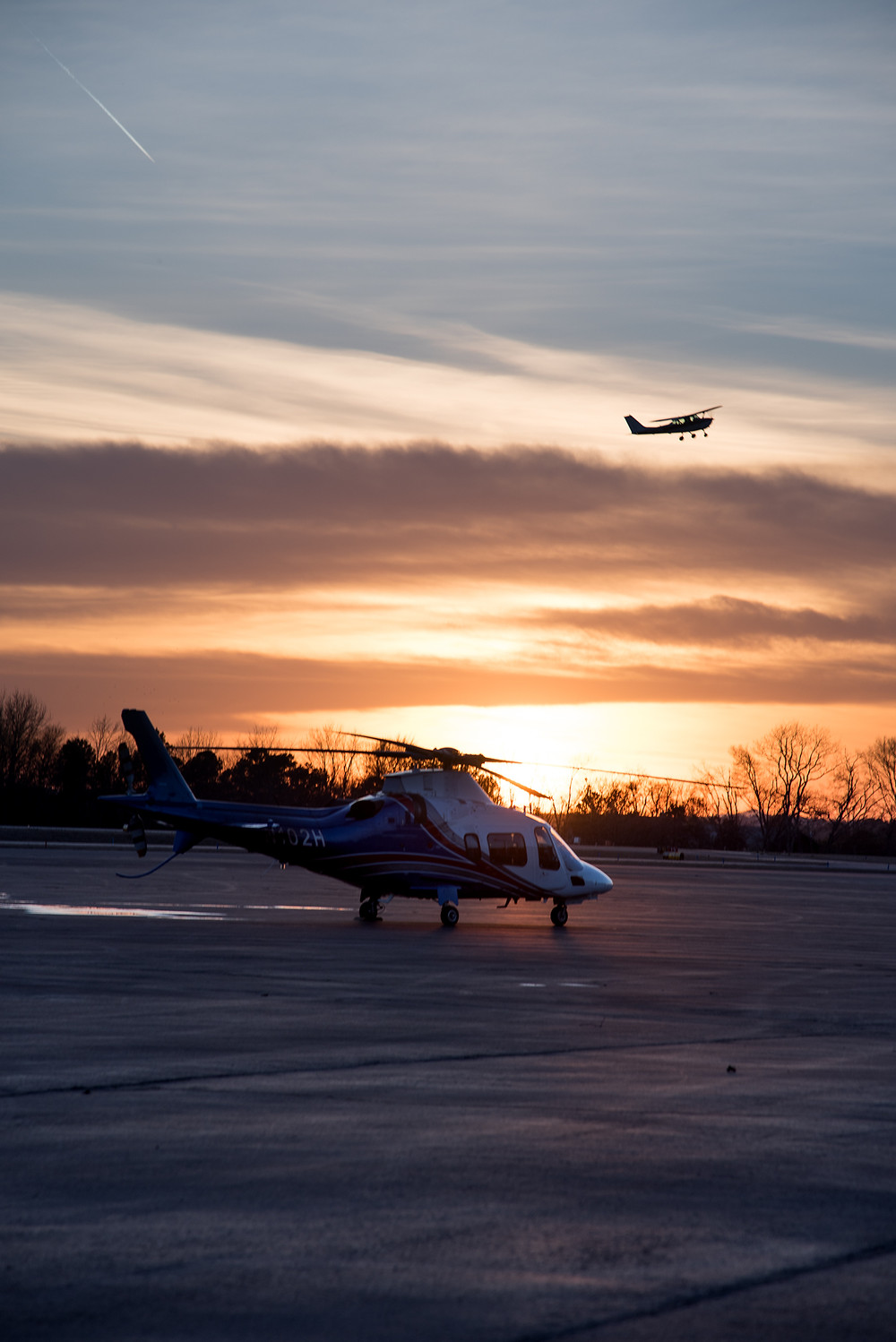Sun sets over Hot Springs Airport, Agusta helicopter parked for the night with Cessna in the pattern doing touch and gos